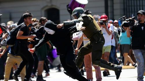 Un manifestante es detenido por la Policía durante una protesta contra el Día de Colón en Santiago de Chile. / Ivan Alvarado / Reuters